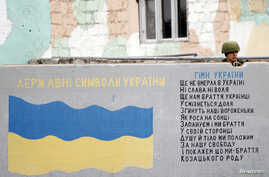 FILE - A Russian serviceman stands guard behind a wall featuring the Ukrainian national flag at the Belbek Sevastopol International Airport in Crimea March 4, 2014.