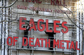 Workers set up ahead a Tuesday's concert by Eagles of Death Metal, at the Olympia music hall, in Paris, Tuesday, Feb. 16, 2016.