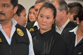 In this photo provided by Peru's Supreme Court communications office, former Peruvian first daughter Keiko Fujimori stands in court where Judge Richard Concepcion ruled that she should be detained as a preventative measure while prosecutors investiga