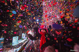 Revellers toss confetti over Times Square from a hotel after the clock struck midnight during New Year's Eve celebrations in New York January 1, 2015.  REUTERS/Keith Bedford (UNITED STATES - Tags: SOCIETY ENTERTAINMENT TPX IMAGES OF THE DAY) - RTR4JS