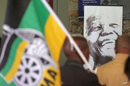 A photo of former South African president, late Nelson Mandela, right, is displayed during a remembrance ceremony in  Qunu, South Africa, Saturday, Dec. 7, 2013.