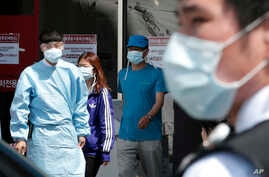 Hospital workers and visitors wearing masks pass by a precaution against the MERS, Middle East Respiratory Syndrome, virus at a quarantine tent for people who could be infected with the MERS virus at Seoul National University Hospital in Seoul, South