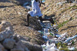 A girl jumps over an open sewage in Port-au-Prince, Sept. 4, 2012.