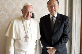 Pope Francis poses with World Bank President Jim Kim as they meet at the Vatican October 28, 2013.