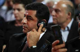 Pro-Kurdish People's Democratic Party leader Selahattin Demirtas listens to Greek Prime Minister Alexis Tsipras' speech to his party congress in Athens, Oct. 13, 2016.