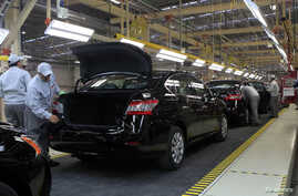 FILE - Employees work at a production line before the opening of Nissan's new plant in Aguascalientes, Mexico, Nov. 12, 2013.