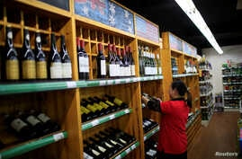 A staff checks on bottles of wine at a supermarket in Shanghai, China, June 2, 2016.
