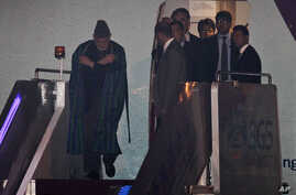 Afghanistan President Hamid Karzai, left, is escorted by officials as he walks out of an airplane upon his arrival in Beijing for the Shanghai Cooperation Organization (SCO) summit, June 5, 2012.