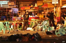 Philippine police officers look at dead victims after an explosion at a night market that has left about 10 people dead and wounded several others in southern Davao city, Philippines late Friday Sept. 2, 2016.
