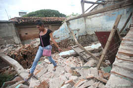 Peregrina, 26, an indigenous Zapotec transgender woman also know as Muxe, walks on the debris of her house destroyed after an earthquake that struck on the southern coast of Mexico late Thursday, in Juchitan, Mexico, Sept. 10, 2017.
