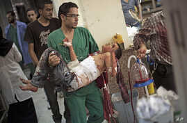 A doctor carries a severely wounded Syrian boy in the Dar El Shifa hospital, in Aleppo, Syria, Oct. 4, 2012 after the child was hit by Syrian Army shelling.