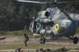 Members of the National Guard of Ukraine jump out a MI-8 helicopter during military tactical exercises at a training base near Kiev, Ukraine, July 22, 2015. REUTERS/Valentyn Ogirenko - RTX1LCJK