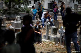 People grieve during the funeral of Javier Rivas, one of the inmates who died during a riot and fire in the cells of the General Command of the Carabobo Police, at the cemetery in Valencia, Venezuela, March 29, 2018.