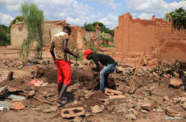Two men dig up bricks to re-use from a destroyed church in Kapende, a Congolese neighbourhood in Lucapa, Angola, Oct. 19, 2018.