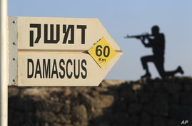 A sign showing the distances to Damascus and a cut out of a soldier are seen at an army post from the 1967 war at Mt. Bental in the Golan Heights, overlooking Syria, July 24, 2012.