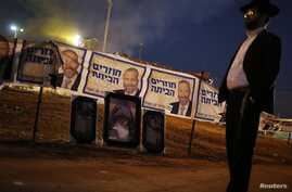 An ultra-Orthodox Jew stands near Shas campaign banners that depicts party leader Aryeh Deri (top) and near pictures of Rabbi Yisrael Abuhatzeira, a Moroccan-born sage and kabbalist also known as the Baba Sali, during an annual pilgrimage to the Rabb