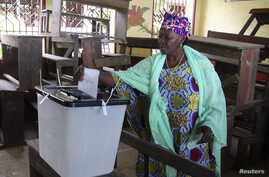 A woman casts her ballot at a polling station in Guinea's capital Conakry, Sept. 28, 2013.