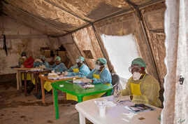 Health workers await patients to screen against the deadly Ebola virus at the Kenema Government Hospital in the Eastern Province in Kenema, 300 kilometers, (186 miles) from the capital city of Freetown, Sierra Leone.