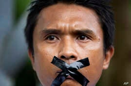 A Myanmar journalist with his mouth sealed with tape, symbolizing the government's recent crackdown on media, protest outside Myanmar Peace Center where President Thein Sein attends a meeting in Yangon, Myanmar, July 12, 2014.