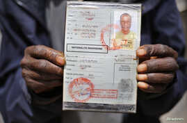 An African migrant shows his ID at a detention centre in Zawiya, northern Libya, May 27, 2014.