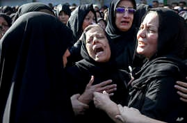 FILE - In this file photo dated, Sept. 24, 2018, families of victims of a terror attack on a military parade in the southwestern city of Ahvaz, Iran, that killed 25 people mourn at a mass funeral in Ahvaz.  A Norwegian citizen of Iranian descent was