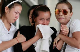 Noppawan Chairat, center, the mother of two children killed in Sunday's bomb attack on an anti-government protest site, Noppawan Chairat, is held by her family members as they wait for their bodies at a hospital in Bangkok, Thailand, Monday, Feb. 24,