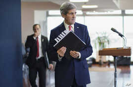 U.S. Secretary of State John Kerry picks up his notebook after answering questions from members of the media before his departure from Ben Gurion International Airport in Tel Aviv on Friday, Dec. 6, 2013.