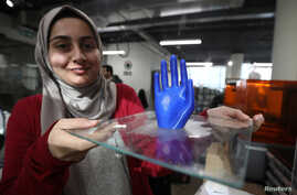 An employee shows a 3D-printed prosthetic hand, created at the FabLab in city of Irbid, Jordan, Feb. 26, 2019.