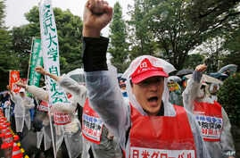 Protesters shout an anti-security bills slogan during a rally in rains in front of the Parliament building in Tokyo Thursday, Sept. 17, 2015.