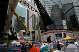 A man walks some tents set up by pro-democracy protesters in an occupied area outside government headquarters in Hong Kong's Admiralty district, Nov. 13, 2014.