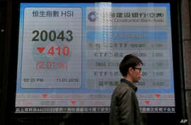 A man walks past an electronic board showing Hong Kong share index outside a local bank in Hong Kong, Jan. 11, 2016.