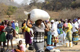 A woman carries a bag of maize distributed by the United Nations World Food Program (WFP) in Mwenezi, about 450 kilometers (280 miles) south of Harare, Zimbabwe, Sept. 9, 2015.