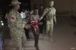 Somali security forces escort a man who was rescued from Pizza House. Somali security forces ended an al-Shabab siege of two Mogadishu restaurants early Thursday morning. About two dozen people were killed.