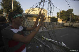 A member of the Muslim Brotherhood and supporter of ousted Egyptian President Mohamed Morsi holds onto barbed wire as he shouts slogans against the military and interior ministry near El-Thadiya presidential palace in Cairo, Sept. 20, 2013.