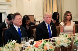 President Donald Trump with first lady Melania Trump, right, welcome South Korean President Moon Jae-in, left, during a dinner in the State Dining Room of the White House in Washington, June 29, 2017.