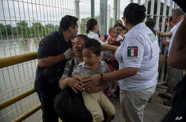 A Honduras migrant mother and her son walk through the bridge after crossing the border between Guatemala and Mexico, in Ciudad Hidalgo, Mexico, Oct. 20, 2018.