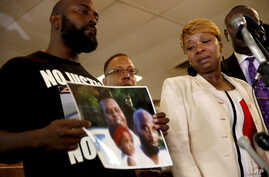 Lesley McSpadden, right, the mother of 18-year-old Michael Brown, watches as Brown's father, Michael Brown Sr., holds up a family picture of himself, his son, top left in photo, and a young child during a news conference, Aug. 11, 2014, in Ferguson,