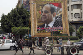 An Egyptian man on horse cart rides past a huge banner for Egypt's former army chief Abdel Fattah al-Sisi in downtown Cairo, May 6, 2014.