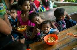 Franyelis, 8, feeds her baby brother Joneiber as their mother Francibel Contreras holds a bowl of scrambled eggs and rice, at a soup kitchen in the Petare slum, Caracas, Venezuela, Feb. 14, 2019..