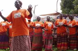 Orange-shirted women promote the health benefits of the orange-fleshed sweet potato during a community theater performance in Uganda.