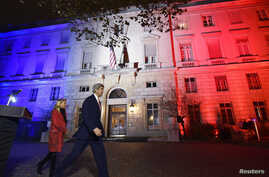 U.S. Secretary of State John Kerry (C), next to U.S. ambassador to France Jane D. Hartley, leaves after delivering a speech at the U.S. embassy in Paris illuminated with the colors of the French national flag, Nov. 16, 2015.