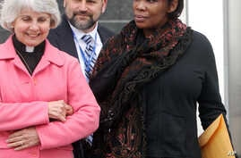 FILE - Beatrice Munyenyezi, right, leaves the federal courthouse in Concord, New Hampshire, April 12, 2012.