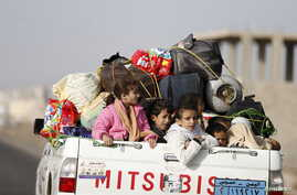 Children ride on the back of a pick-up truck with their luggage as they flee Saudi-led air strikes in Sanaa April 6, 2015. Foreign nationals were on their way out of Yemen on Monday as 12 days of strikes by a Saudi-led coalition have failed to halt t