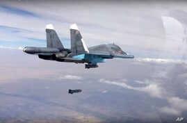 In this photo made from the footage taken from Russian Defense Ministry official web site on Oct. 9, 2015, a bomb is released from Russian Su-34 strike fighter in Syria.