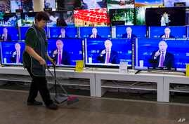 A cleaner walks past a store in Moscow with TV sets showing Russian President Vladimir Putin during his annual live call-in show, June 15, 2017.
