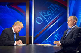 """Republican presidential candidate Donald Trump, left, signs his book for Bill O'Reilly, right, during his appearance on Fox's news talk show """"The O'Reilly Factor,"""" Nov. 6, 2015, in New York."""