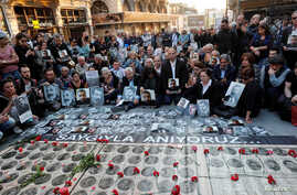 FILE - Human rights activists hold portraits of victims during a demonstration to commemorate the 1915 mass killing of Armenians in the Ottoman Empire, in central Istanbul, Turkey, April 24, 2018.