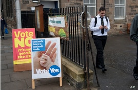 A school pupil walks away from a polling place after casting his vote, as anyone aged over 16 can vote in the Scottish independence referendum, in Edinburgh, Scotland, Sept. 18, 2014.