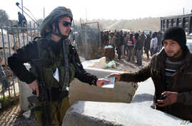 A member of the Israeli security forces hands a Palestinian worker his ID upon his  transport out of the Tekoa settlement south of Jerusalem on Jan. 18, 2016, after Israeli authorities denied them entry following a stabbing attack.
