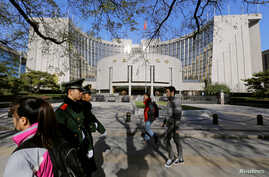 People walk past the headquarters of the People's Bank of China as two police officials patrol the area in Beijing Nov. 20, 2013.